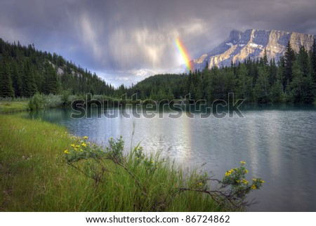 A beautiful rainbow over Mount Rundle at Cascade Ponds near Banff in Banff National Park Canada. These picturesque ponds are surrounded by the Rocky Mountains. - stock photo