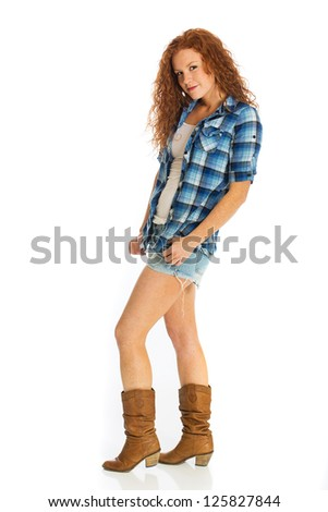 A beautiful red haired girl wearing short denim shorts - stock photo