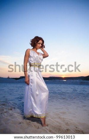 A beautiful red-haired lady in a greek style dress in the rays of the setting sun