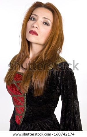 A beautiful, red head, Hispanic woman in a red and black dress in front of a white background. - stock photo