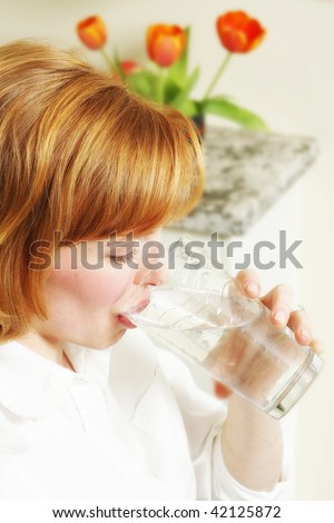 a beautiful redhead takes a drink of clean natural water