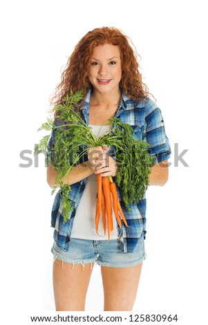 A beautiful redhead woman with a farm fresh batch of carrots. - stock photo