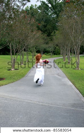 A beautiful redheaded bride running away, or rushing late