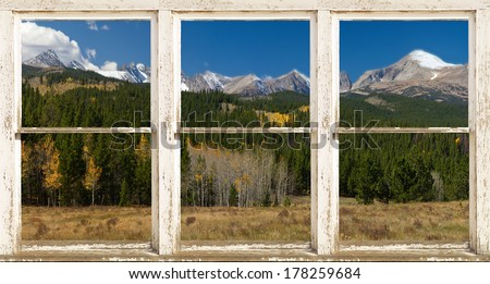 A beautiful Rocky Mountain Continental Divide rustic picture window frame panorama view with clouds hanging on the mountains, a light dusting of snow and fall colors in the air.  - stock photo