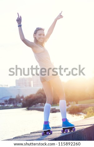 A beautiful roller skater woman during the sunset, outdoor - stock photo