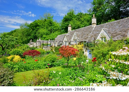 A Beautiful Row Of Cotswold Country Cottages And Gardens In Summer With Blue Sky Clouds