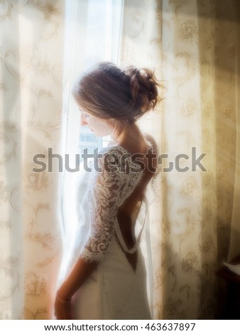 a beautiful Russian bride posing in the early morning at the window, soaking up the first rays of the sun