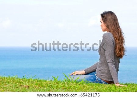 A beautiful sad and unhappy young woman sitting in the green grass looking at the ocean - stock photo