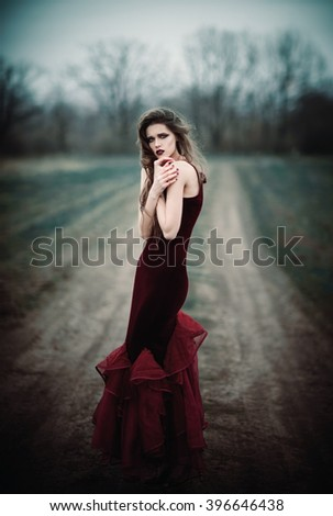 A beautiful sad girl in the autumnal field - stock photo