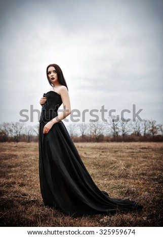 A beautiful sad goth girl stands in the autumnal field - stock photo