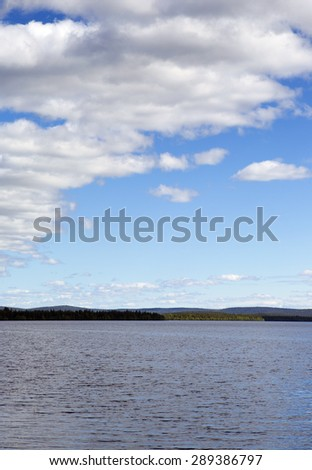 A beautiful scene in Finland in the summer time. Some clouds in the sky giving a deep contrast to the image.