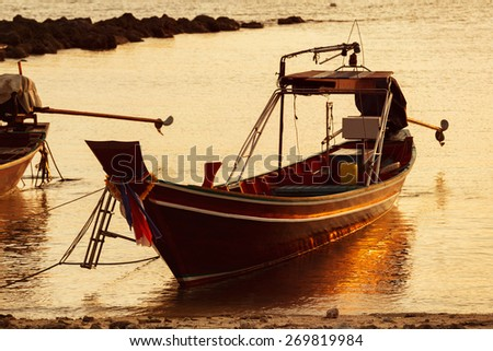 A beautiful scene of a boat reflecting in water at sea shore at orange sunset background. - stock photo