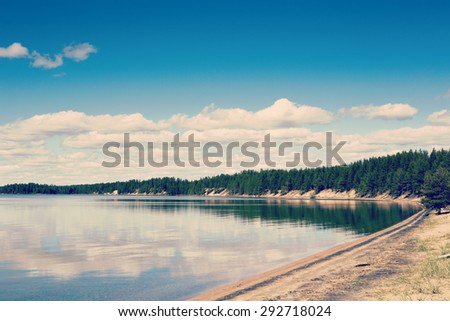 A beautiful scene with crystal clear water in Finland in the summer time. Some clouds in the sky giving a deep contrast to the image. Image has a vintage effect applied. - stock photo