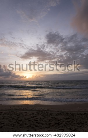 A beautiful seascape view of a tropical beach at Phuket, Thailand. Many clouds at the sunset sky.