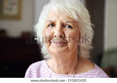 A beautiful senior woman looking at the camera with pursed lips - stock photo