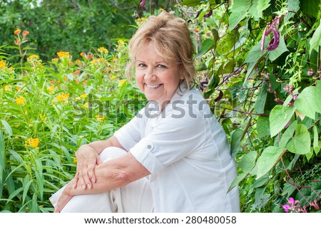 A beautiful senior woman sits in front of a lush green background of flowering plants.  She is dressed in white clothing and is smiling broadly. - stock photo
