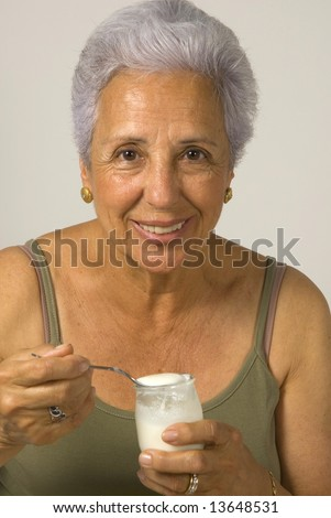 A beautiful seventy five year old woman eating a yogurt after doing exercise. - stock photo