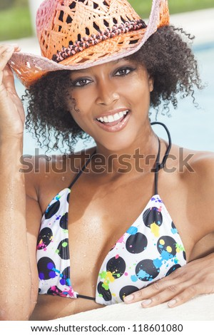 A beautiful sexy young African American girl or young woman wearing a bikini and straw cowboy hat laughing on the side of a swimming pool. - stock photo