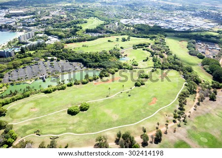 A beautiful shoreline golf course as viewed from above from a door-free helicopter in Kauai Hawaii. - stock photo