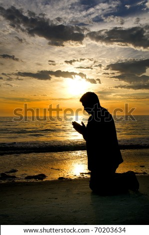 A beautiful silhouette of a man praying at the ocean with his hands folded. - stock photo