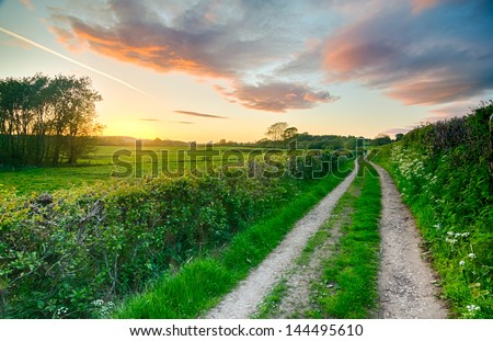 A beautiful sky after sunset on a summer farm track and fields in England, UK with red, orange and pink sky elements - stock photo