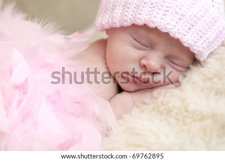 A beautiful sleeping newborn baby girl, with pink hat and pink boa, copy space, soft focus - stock photo