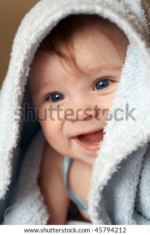 A beautiful smiling baby wrapped in a furry blue blanket A beautiful smiling baby wrapped in a furry blue blanket - stock photo