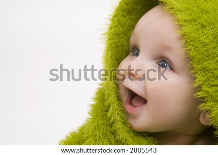 A beautiful smiling baby wrapped in a furry green blanket or towel