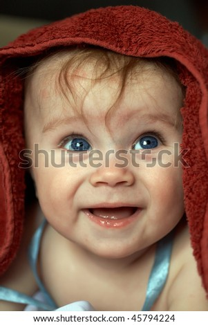 A beautiful smiling baby wrapped in a furry red blanket - stock photo