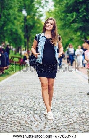 A beautiful smiling pregnant woman in a black tight dress and blue jeans jacket with backpack walking on the alley in the park.