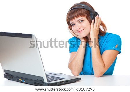 a beautiful smiling red-haired girl with a laptop is listening to the music. isolated on white background