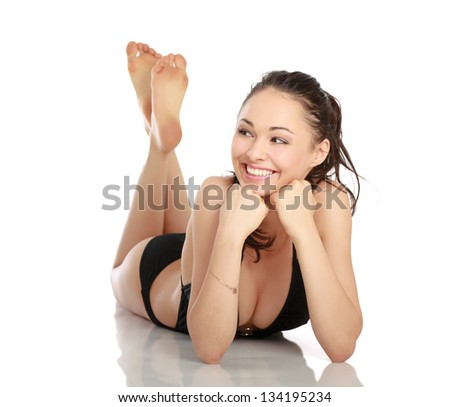 A beautiful smiling woman in a black swimsuit is lying on the floor
