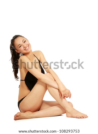 A beautiful smiling woman in a white swimsuit is siiting on the floor