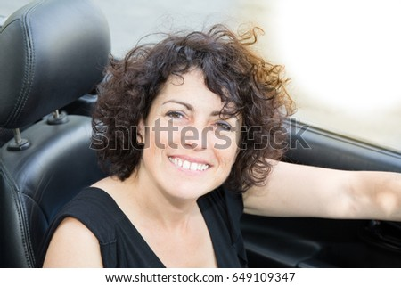 A beautiful smiling woman sitting in his convertible car