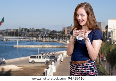 A beautiful smiling woman teenager pointing her fingers while on a vacation or holiday - stock photo