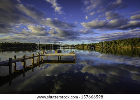 A beautiful southern United States sunset reflecting on a calm lake showing the colors, clouds and far shoreline on the surface. With a wooden dock or pier, mooring balls and a floating trampoline - stock photo