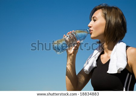A beautiful sporty caucasian girl drinking water after exercise - stock photo