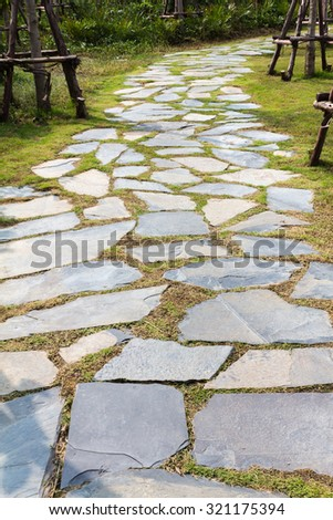 A beautiful stone Walkway on green grass in garden - stock photo