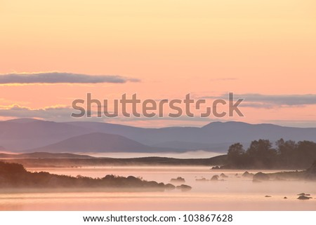 A beautiful sunrise on Rannoch Moor in Scotland with a great view over the moors with morning fog. - stock photo