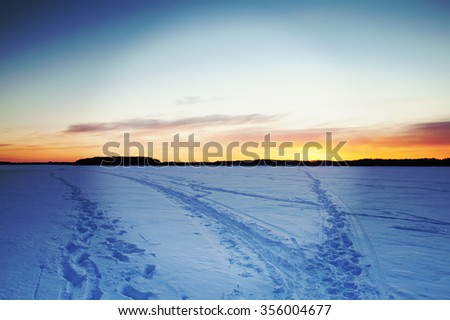 A beautiful sunset on the lake during winter. Some ski tracks and footprints are in the snow.