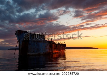 A beautiful sunset over a rusty freighter acting as a breakwater for a harbor - Powell River, British Columbia, Canada.  - stock photo