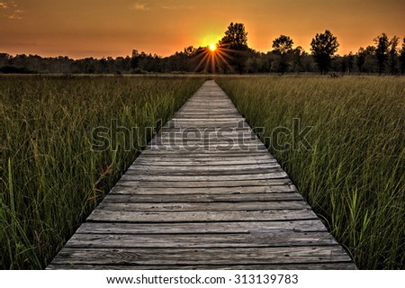 A  beautiful sunset scene along a  wood boardwalk with the boardwalk leading right into the setting sun. Find this boardwalk at Irwin Prairie State Nature Preserve in Northwest Ohio.