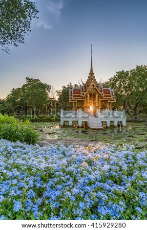 A beautiful sunset through a shrine on a lake covered in lilies with blue flowers at the front - stock photo