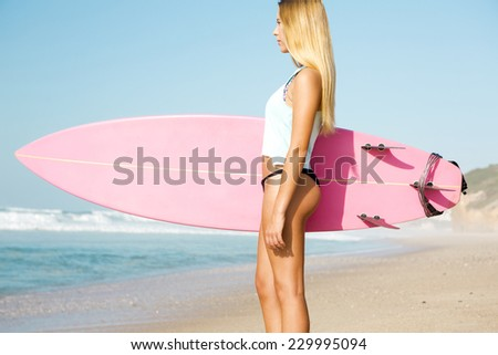 A beautiful surfer girl looking at the beach with her surfboard