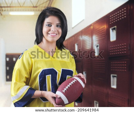 A beautiful teen girl happily holding a football in a locker room.  - stock photo