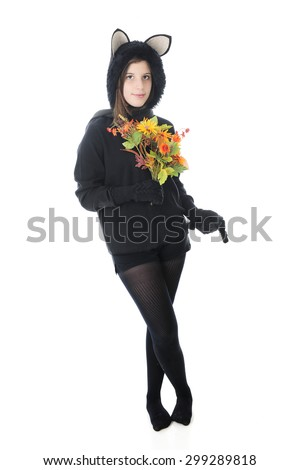 A beautiful teen girl in a black cat outfit, holding a bouquet of fall flowers in one hand and her tail in the other.  On a white background.