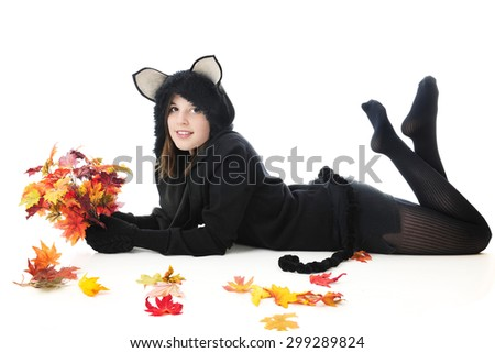 A beautiful teen girl in a black cat outfit, relaxed on her belly surrounded by colorful autumn leaves.  On a white background. - stock photo