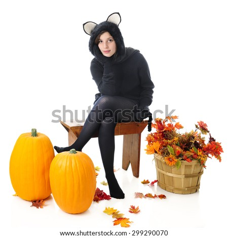 A beautiful teen girl in a black cat outfit, waiting on a bench with pumpkins and a basket of fall foliage nearby.  On a white background. - stock photo