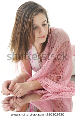A beautiful teen girl looking down as she relaxes on a floor mirror.  On a white background. - stock photo