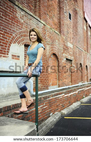 A beautiful teen girl sitting on the railing of a rustic brick building.